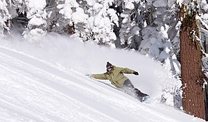 Snowboarding - A snowboarder making a turn in fresh snow.