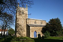 A stone church seen from the south with, on the left, an embattled tower with pinnacles, and to the right a nave with clerestorey, aisle, and pointed doorway
