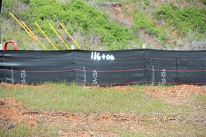 Linear referencing - A station number written on a silt fence at a construction site