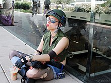 A young woman dressed as Tank Girl sitting down smoking a cigarette