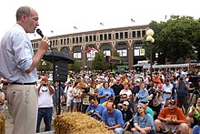 McCotter stands outside with a microphone before a podium and bale of hay facing a seated crowd