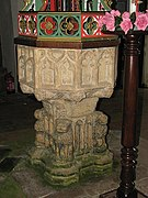 the 15th-century octagonal font with bowl panels decorated with tracery with the underside of the bowl supported by carved demi-figures of angels. The pedestal has four hunched lions, one to each corner with a double tracery panel between each lion.