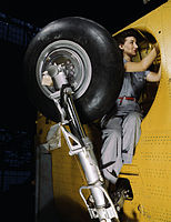 This woman worker at the Vultee-Nashville is shown making final adjustments in the wheel well of an inner wing before the installation of the landing gear.jpg