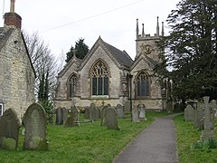 Gray three bay building with arched windows. Tower behind and gravestones in the foreground.