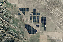A satellite image of what look like semi-regularly spaced swathes of black tiles set in a plain, surrounded by farmland and grass lands