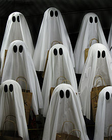 Lots of small sheets-with-eyes-style ghosts holding baskets