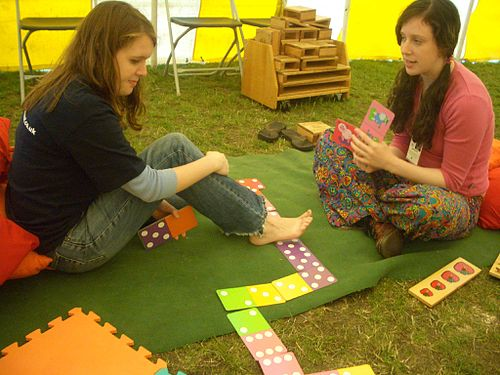 Two women playing dominoes on the grass
