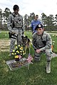U.S. Air Force Airman 1st Class Paul Reinhart, kneeling, with the 10th Security Forces Squadron, places a flag at the grave marker of his uncle, Capt. Daniel Reinhart, a 1980 graduate of the U.S. Air Force 130520-F-JM997-885.jpg