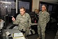 U.S. Air Force Tech. Sgt. Kelly Gonzalez, left, with the 219th Security Forces Squadron, North Dakota Air National Guard (NDANG), explains aspects of her job to Chief Master Sgt. James Gibson, the senior 130521-Z-WA217-213.jpg