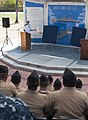 U.S. Navy Capt. Randy Garner, at podium, commodore of Commander Littoral Combat Ship Squadron 1, gives his remarks during the littoral combat ship Pre-Commissioning Unit Jackson's (LCS 6) crest unveiling 130827-N-YQ852-028.jpg