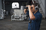 U.S. Navy Seaman Mack Kameron looks through binoculars while standing watch on the fantail of the aircraft carrier USS Nimitz (CVN 68) June 10, 2013, while underway in the Indian Ocean 130610-N-LP801-011.jpg