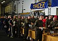U.S. Sailors and Marines move through a buffet line in the hangar bay of amphibious assault ship USS Makin Island (LHD 8) during a modified steel beach picnic Dec. 11, 2011, while under way in the Philippine 111211-N-FH966-024.jpg