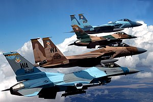 57th Wing - A flight of Aggressor F-15 Eagles and F-16 Fighting Falcons fly in formation. The jets are assigned to the 64th and 65th Aggressor squadrons at Nellis Air Force Base. Identified aircraft are F-16C Block 32C 86-251; Block 25E 84-1299; F-15C-27-MC 80-0010 and F-15D-39-MC 85-129.