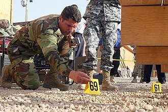 Criminal investigation - Al Asad Air Base, Iraq, – An Iraqi police officer in the Basic Criminal Investigation Course here lays down numbered tabs on a mock crime scene to mark evidence during the class' final exercise.