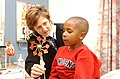 US Navy 030328-N-0000W-001 Lt. Marjorie Nasin uses a Japanese toy to help a young patient blow air as she listens to his breathing.jpg