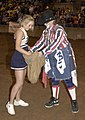 US Navy 031229-N-0399H-039 U.S. Naval Academy Cheerleader Midshipman 4th Class Jaime Bradley, from The Woodlands, Texas, picks a cow chip from a bag held by a rodeo clown in Reliant Arena.jpg
