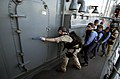 US Navy 050923-N-9288T-177 U.S. Navy Senior Chief Operation s Specialist Terry Schweizer, prepares to enter a hatch during a Visit, Board, Search and Seizure (VBSS).jpg