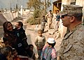 US Navy 051107-N-1261P-035 A U.S. Marine speaks to local Pakistanis during a walking tour of Muzafarrabad, Pakistan.jpg