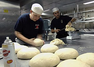 US Navy 060812-N-5914D-002 Culinary Specialist Seaman Douglas Markusson, and Aviation Boatswain's Mate Fuels Airman John Faulds, assigned to the amphibious assault ship USS Boxer (LHD 4) prepare to bake bread for the next day's.jpg