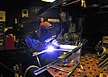US Navy 090113-N-4774B-042 Hull Maintenance Technician Brian Winter welds cross braces to an aluminum chair.jpg