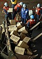 US Navy 100119-N-2000D-035 Sailors aboard the amphibious dock landing ship USS Carter Hall (LSD 50) load meals-ready-to-eat (MREs) in the claw of a bulldozer to transport ashore to earthquake victims.jpg