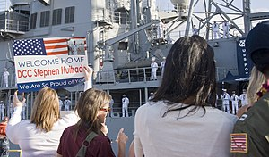 US Navy 120213-N-QG393-019 Friends and family members of Sailors aboard the guided-missile cruiser USS Port Royal (CG 73) greet them with signs to.jpg