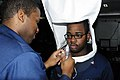 US Navy 120214-N-WV964-009 Information Technician 2nd Class Raymond Jackson performs a respiratory fitting test on Hull Technician 3rd Class Adrine.jpg