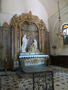 Retable en bois polychrome. Deux statues, dont une du Christ, encadrent un Sacré Cœur. En bas, un aigle doré (référence à Bossuet)