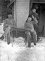 Vinterbild. Två män sitter framför en stuga och en kvinna står bredvid dem - Nordiska Museet - NMA.0057192.jpg