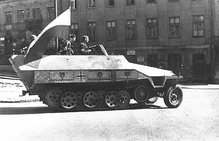 "Captured German Sd.Kfz. 251 from the 5th SS Panzer Division Wiking, and pressed into service with the 8th ""Krybar"" Regiment. The soldier holding a MP 40 submachine gun is commander Adam Dewicz ""Gray Wolf"", 14 August 1944 Warsaw Uprising - Captured SdKfz 251 (1944).jpg"