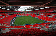The interior of an empty stadium as viewed from its upper tier of seating. The seats are a vivid red and the pitch is a vivid green. The pale grey sky is visible through an opening in the ceiling above the pitch.