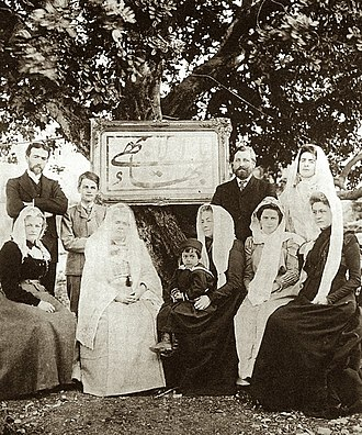 `Abdu'l-Bahá - Early Western Bahá'í pilgrims. Standing left to right: Charles Mason Remey, Sigurd Russell, Edward Getsinger and Laura Clifford Barney; Seated left to right: Ethel Jenner Rosenberg, Madam Jackson, Shoghi Effendi, Helen Ellis Cole, Lua Getsinger, Emogene Hoagg