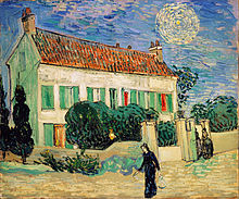 A white two-storey house at twilight, with two cypress trees on one end, and smaller green trees all around the house, with a yellow fence surrounding it. Two women are entering through the gate in the fence; a woman in black walks on by going towards the left. In the sky, there is a bright star with a large yellow halo around it