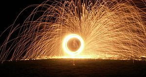 Fire performance - A fire performer spinning poi consisting of lit wire wool in chicken wire cages, dipped first in paraffin. Long-exposure photography captures the trails created by sparks.