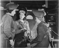 Women are welders discuss the production of motor mounts and welded parts in a welding booth at the Inglewood... - NARA - 195478.tif