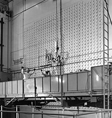 Zwei Arbeiter auf einer beweglichen Plattform, ähnlich der von Fensterputzern, stecken eine Stange in eines der vielen kleinen Löcher in der Wand vor ihnen.