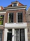 foto van Pand met bakstenen voor- en achtergevel voorzien van rechte kroonlijsten en geprofileerde natuurstenen dorpels onder de vensters in de voorgevel