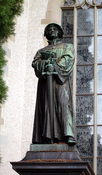 Theology of Huldrych Zwingli - Statue of Zwingli in Zürich where he holds the Bible in one hand and a sword in the other.