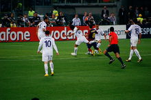 Several men in white shirts stand around a man in a blue-and-red shirt who is falling to the ground.