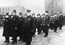 eine angetretene Gruppe von Polizisten in langen schwarzen Mänteln, welche alle eine weiße Maske tragen