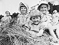 A group of children sitting on a large pile of hay outside Chapel Cleeve Nursery in Washford, Somerset during 1942. D9211.jpg
