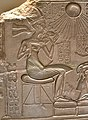 Akhenaten with one of his girls, detail of an altarpiece of a shrine. God Aten and his cartouches appear. C. 1345 BCE. From Amarna, Egypt. Neues Museum.jpg