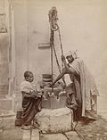 Algerian man and boy drawing water from a well (circa 1892).jpg