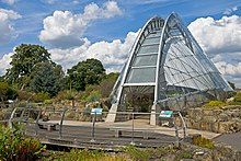 A narrow semicircular building of glass and steel latticework stands at the right, set amid an area of worked rock with a line of deciduous trees in the rear left, under a blue sky filled with large puffy white clouds. In front of it, curving slightly away to the left, is a wooden platform with benches on it and a thin metal guardrail in front of a low wet area with bright red flowers