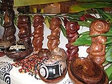 Photo de statuettes de tikis en bois et d'autres objets artisanaux.
