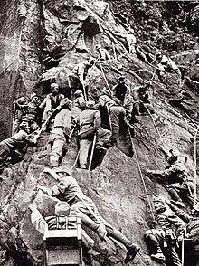 black and white photograph of men in uniforms climbing a steep rock face using ropes