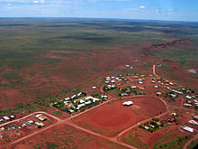 An aerial view of a small settlement, showing about seventy rooftops, red dirt roads and a dirt oval, with dry scrubland receding into the distance