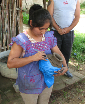 Barro negro pottery - A woman cutting designs into unfired barro negro pottery in San Bartolo Coyotepec, Oaxaca, Mexico.