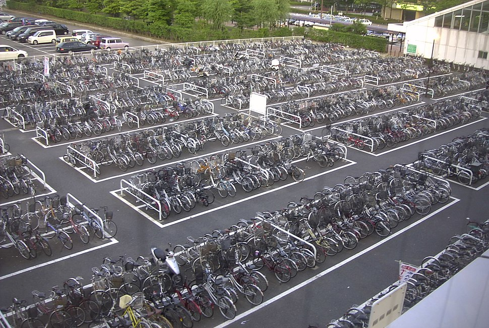 Hundreds of bicycles, grouped in rectangular parking places with driving paths in between.