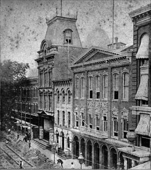 Brooklyn Theatre fire - Washington Street entrance before the fire, looking north toward Johnson Street. The theatre is distinguished by its mansard roof. Its 'L' shaped lot wrapped around the Dieter Hotel, here partially obscured by trees.